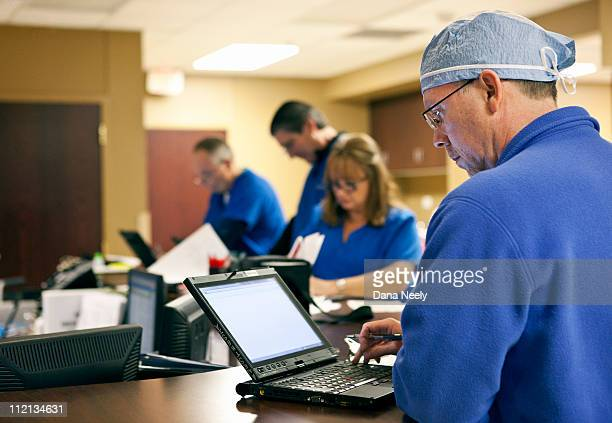 Surgeon reviewing patient's chart on laptop.