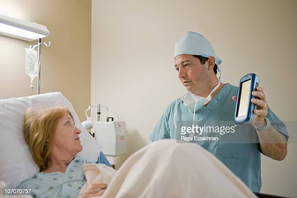 surgeon shows device to control back pain - newhealth stock pictures, royalty-free photos & images