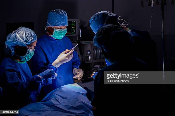 surgeon using sutures during operation in hospital operating room - suture stock photos and pictures