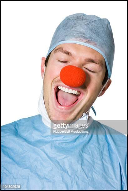 surgeon wearing a creepy clown nose - nariz de payaso fotografías e imágenes de stock