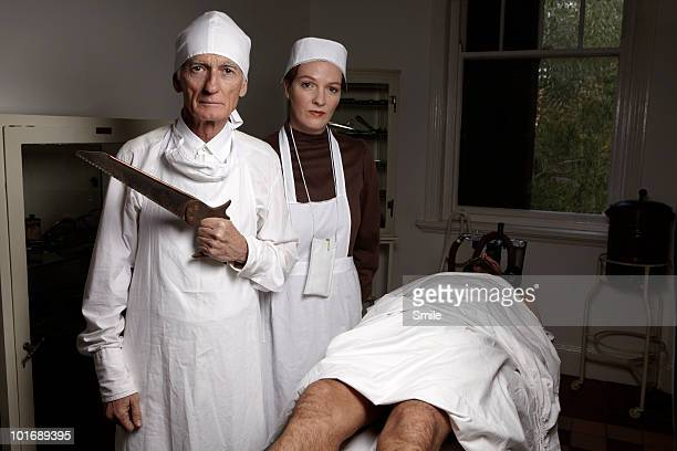 surgeon with saw, antiquated theatre  - female autopsy photos stock photos and pictures