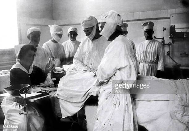 Surgeons doing surgery in hospital 10's a nurse is ready to give anaesthetic if the patient comes round