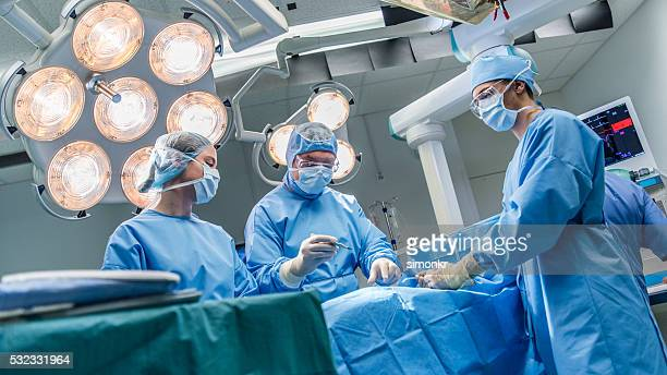 surgeons in operating theatre - medical procedure stock pictures, royalty-free photos & images