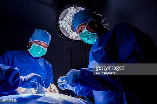 Surgeons performing complicated surgery on patient in operating room