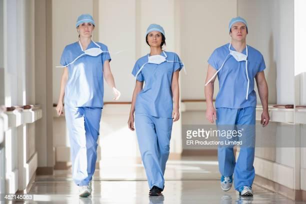 surgeons walking down hospital corridor - beschermend masker werkkleding stockfoto's en -beelden