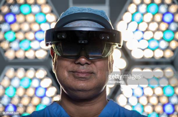 Surgeon Shafi Ahmed poses for a photograph wearing a Microsoft Corp HoloLens headset inside his operating theater at the Royal London Hospital part...
