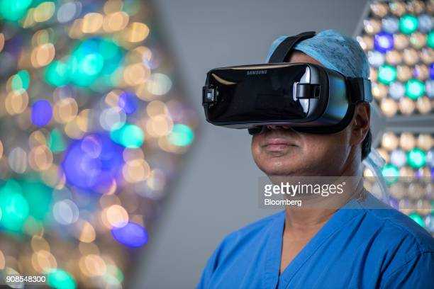 Surgeon Shafi Ahmed poses for a photograph wearing a Samsung Electronics Co Gear VR headset inside his operating theater at the Royal London Hospital...