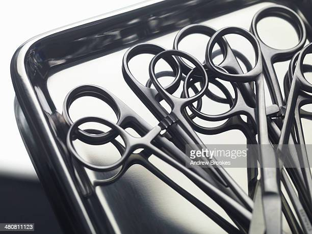 surgical instruments on a stainless steel tray - surgery tools stock photos and pictures