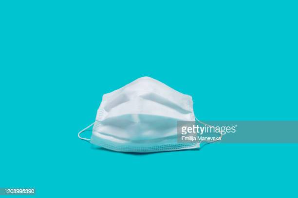surgical mask/ flu mask on blue background - protective face mask stock pictures, royalty-free photos & images
