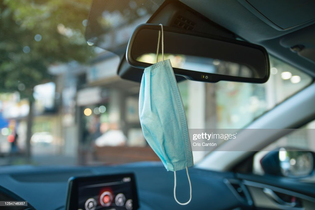 Surgical mask hanging from car rear mirror : Stockfoto