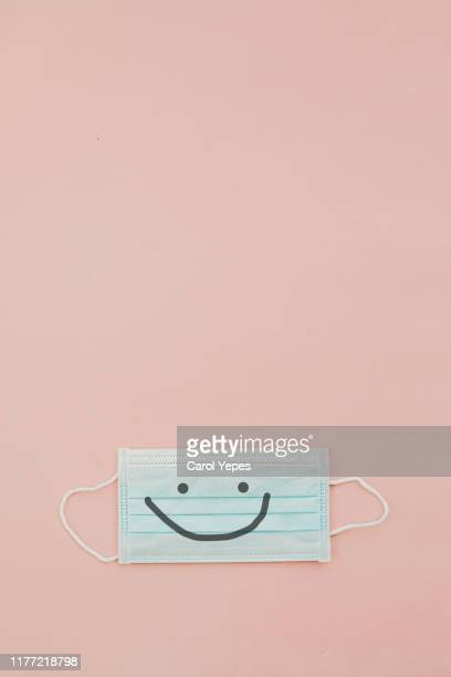 surgical mask in pink with smile .copyspace - grippeschutzmaske stock-fotos und bilder