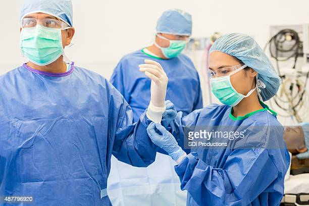 surgical nurse assisting surgeon with gloves and gown in or - operating gown stock pictures, royalty-free photos & images