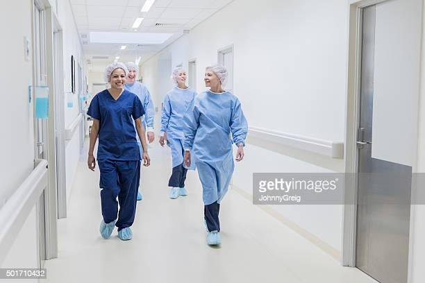 Surgical team walking down hospital corridor, front view
