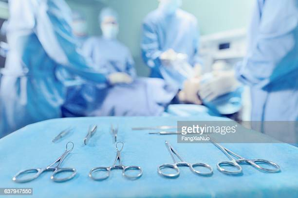 Surgical tools arranged on tray with doctors in operating room