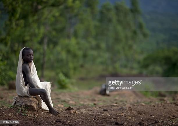 Suri boy sitting in Turgit village Omo valley Ethiopia on July 05 2010 Surma or Suri are sedentary pastoral people living in south west of Ethiopia...