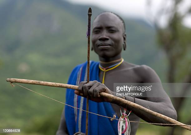 Suri man with a bow and arrow for the blood meal ritual in Turgit village Omo valley Ethiopia on July 05 2010 Blood Meal Like in Rendille or Massais...