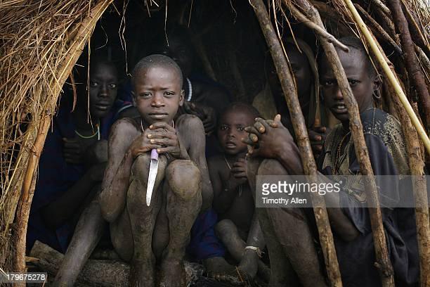 Suri tribal family crouching in hut