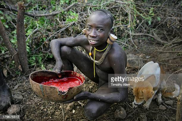suri tribal warrior drinks cow's blood from gourd - naakte jongens stockfoto's en -beelden