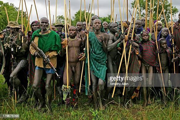 Suri tribal warriors, sticks & guns at Donga