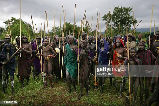 Suri tribal warriors, sticks & rifles at Donga