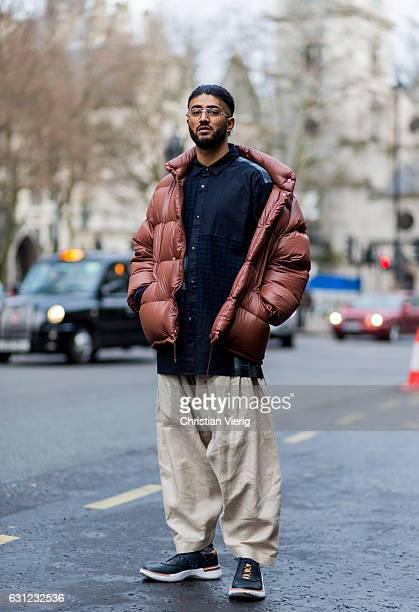 Suril wearing a brown down feather jacket denim shirt wide leg pants boots during London Fashion Week Men's January 2017 collections at KTZ on...