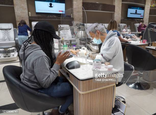 Surin Nguyen, wearing protection gear, works on the nails of a customer at Allure Nail Bar in Atlanta, Georgia on April 24, 2020. - Governor Brian...