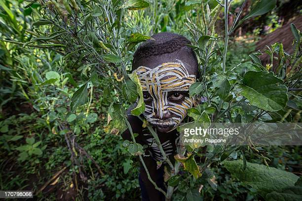 CONTENT] Surma tribe boy with his face painted in the field in the village near kibish ethiopia