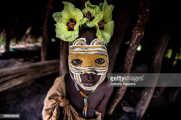 CONTENT] Surma tribe child with face painting and the flowers in the head in the hut in kibish