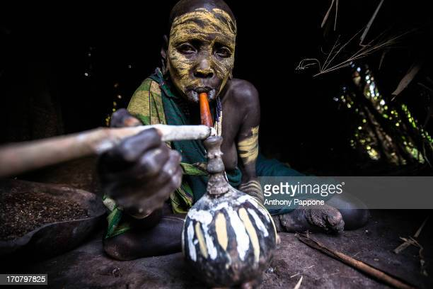 CONTENT] Surma tribe woman with her face painted while smoke from the typical pipe inside the hut in the village near kibish ethiopia
