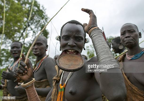 Surma woman wearing a lip plate and copper bracelets in Kibbish village Omo valley Ethiopia on July 04 2010 Piercing and lip plates are a strong part...
