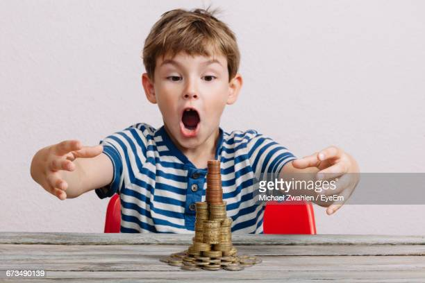 Surprise Boy Looking At Stack Of Coins On Table Against White Background
