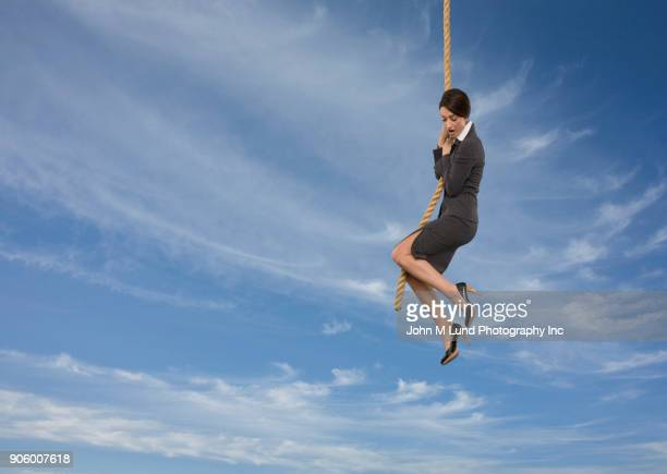 surprise caucasian businesswoman hanging on rope in sky - hanging stock pictures, royalty-free photos & images