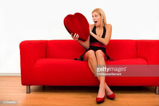 surprise female holding a big heart shape - legs crossed at ankle stock pictures, royalty-free photos & images