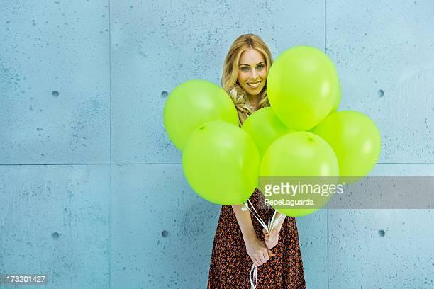Surprise! girl holding green balloons