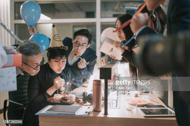 surprise office birthday party celebration blowing birthday candle - 30 39 years stock pictures, royalty-free photos & images