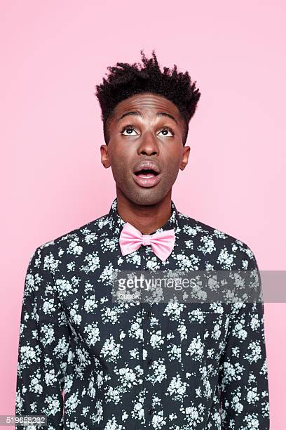 Surprised afro american guy against pink background