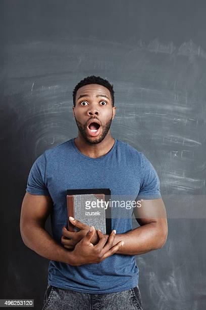 Surprised afro american man against blackboard