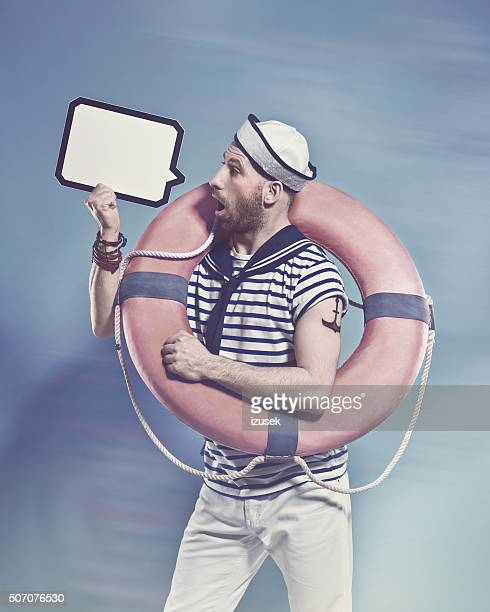 Surprised bearded sailor holding lifebuoy and speech bubble