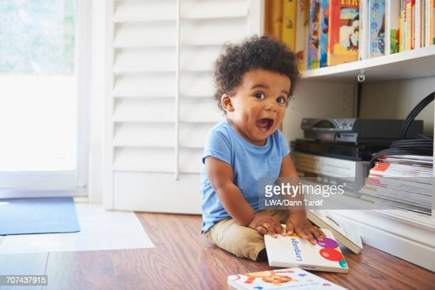 Surprised Black baby boy sitting on floor playing with books