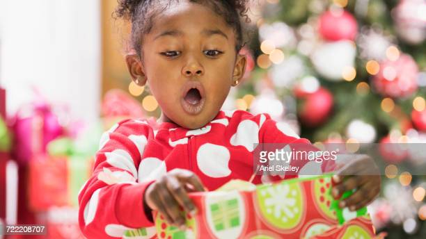 surprised black girl opening gift box on christmas - girls open mouth stockfoto's en -beelden