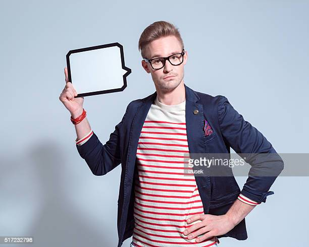 Surprised blonde young man holding a speech bubble