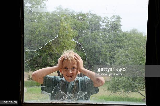 Surprised boy and broken window