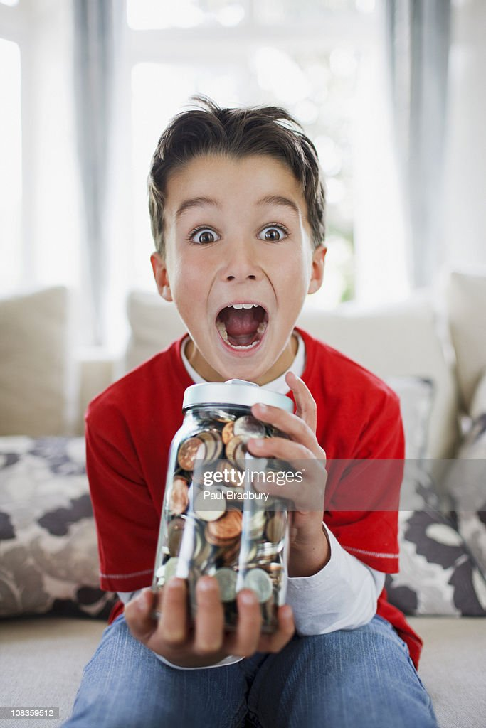 Surprised boy holding jar full of coins : Stock Photo