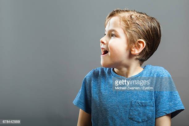 Surprised Boy Looking Away While Standing Against Wall