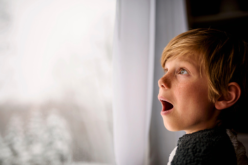 Surprised Boy looking out of the window in winter - gettyimageskorea