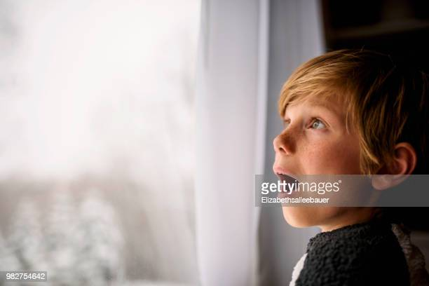 surprised boy looking out of the window in winter - überraschung stock-fotos und bilder