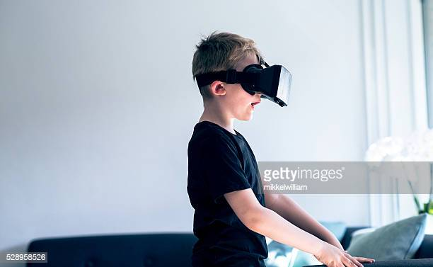 Surprised boy looks into a pair of VR glasses