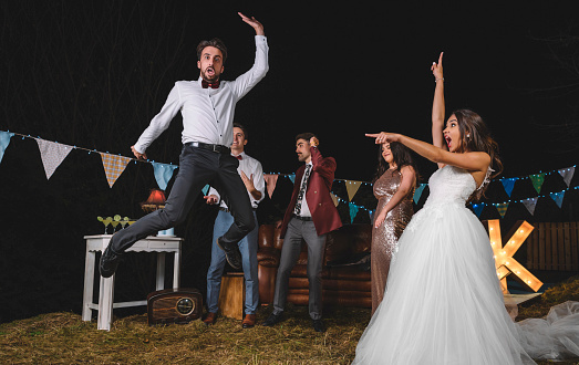 Surprised bride looking at man jumping on a night field party with friends - gettyimageskorea