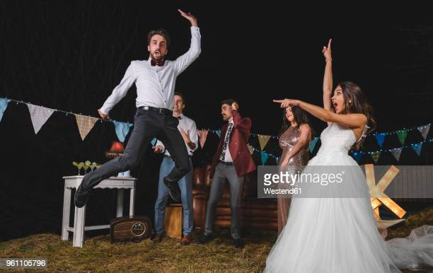 Surprised bride looking at man jumping on a night field party with friends