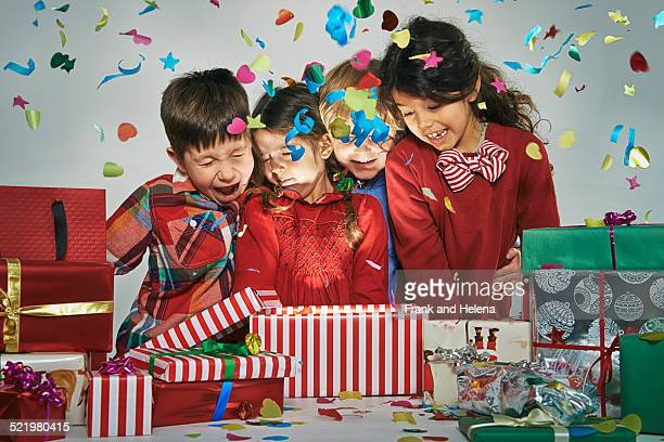 Surprised brothers and sisters unwrapping glowing christmas gift box with exploding confetti